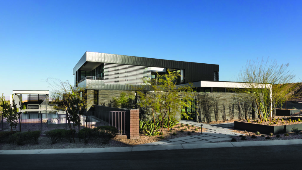 A front view of a desert modern custom home featuring metal planters, iron fencing and steel cladding